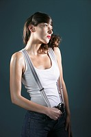 Young woman wearing suspenders, handgun on waist