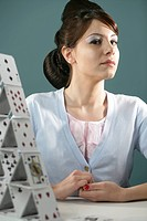 Young woman with trendy hairstyle sitting by house of cards