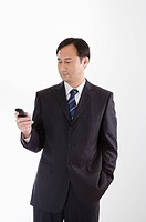 Businessman using mobile phone and looking down, Business People