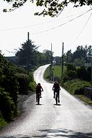 two teenage girls cycling off into the sun along a small narrow country road in county sligo republic of ireland