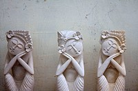 Three white stone figures of women that seem to be sleeping in sitting positions in Ubud, Bali
