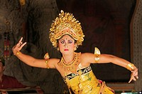 A woman in a traditional costume dancing a Balinese dance in Ubud
