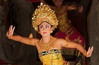 A woman in a traditional costume dancing a Balinese dance in Ubud.