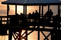 friends gather on dock for weekly Friday social hour at sunset