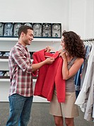 couple shopping holding up pullover