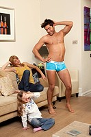 man in underwear showing off to family