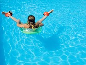 Teenage girl swimming in the pool with floats