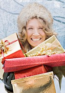 Smiling woman holding Christmas gifts