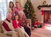 Multi_generation family sitting on sofa near Christmas tree