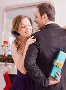 Woman peeking at Christmas gift behind man&#8217;s back