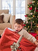 Surprised boy holding Christmas gift
