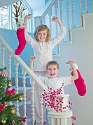 Boy and girl holding Christmas stockings on stairs
