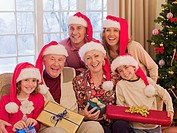 Multi_generation family wearing santa hats and holding Christmas gifts