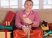 Man with champagne surrounded by Christmas gifts
