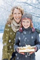 Mother and daughter holding Christmas gift in snow