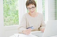 Woman using laptop and holding credit card