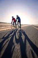 Two men cycling on road