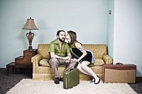 Couple sitting on living room sofa with luggage