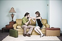 Man kissing womans hand on living room sofa with luggage