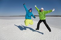 Two Women Jumping on Frozen Lake