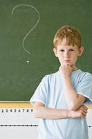 boy thinking next to the board