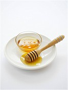 Honey in small dish and on honey dipper