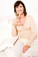 Young woman with a glass of white wine sitting in bed