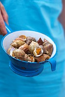 Woman holding sea snails in strainer