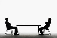 Businessmen facing each other across a table