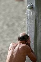 elderly balding tanned man using beach shower at playa de las americas Tenerife Canary Islands Spain
