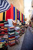 Malta, Gozo, Victoria, Rabat, colourful side street stall selling towels
