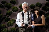Mature man standing with a mature woman and holding a camera and smiling