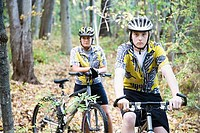 Teenage boy and a woman mountain biking through a forest