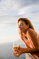 Woman holding a glass of wine and smiling on a sailboat, Tahaa, Tahiti, French Polynesia