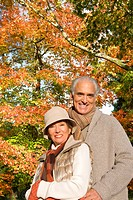 Senior couple hugging in park in autumn