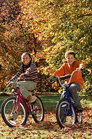 African brother and sister riding bicycles in autumn