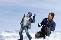 Father and son throwing snowballs