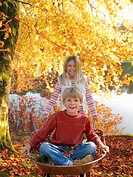 Brother and sister with wheelbarrow on lake shore in autumn