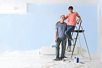 Smiling woman on ladder hugging man next to painted wall