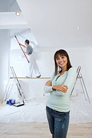 Woman smiling as man on wood plank paints living room wall in background