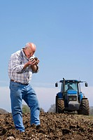 Farmer cupping and smelling soil in field with tractor in background