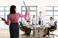 Business people in office applauding businesswoman holding file
