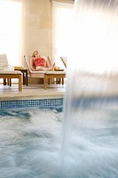 Woman laying on lounge chair near spa swimming pool with waterfall