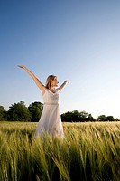 Smiling teenage girl standing in sunny barley field with arms outstretched