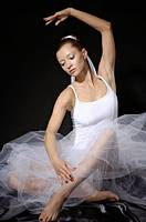 Young woman ballet dancer in white tu-tu dress