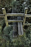 A stile on a footpath with winter frost