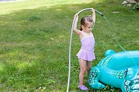 4-year old girl filling her inflatable pool with water  MR