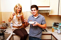 A young couple in a kitchen eating soup