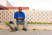 Skateboarder youth sitting on curb listens to personal music player