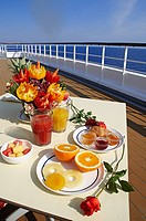 Greece, Cyclades, cruise in Aegean Sea, boat cruise, breakfast on the deck, vegetables sculpture, red rose, orange juice and tomato juice and fruits o...